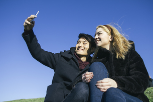 Young couple taking a selfie with smartphoneの写真素材 [FYI04333762]
