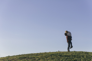 Young couple kissing on a hill in front of blue skyの写真素材 [FYI04333763]