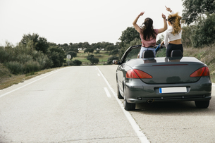 Women having fun in a convertible car on a country roadの写真素材 [FYI04333765]