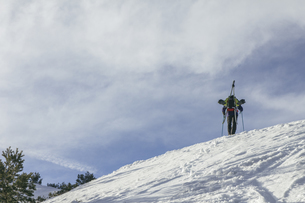Spain, Man with skis in a backpack on top of a snowy hill, Pの写真素材 [FYI04333776]