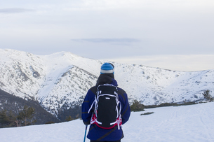 Back of a skier observing a snowy mountain landscapeの写真素材 [FYI04333780]