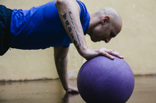 Man doing push-ups with a medicine ballの写真素材 [FYI04333781]