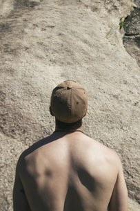 Back of a shirtless man with a gap looking at a wall beforeの写真素材 [FYI04333783]