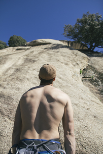 Back of a shirtless man with a gap looking at a wall beforeの写真素材 [FYI04333786]