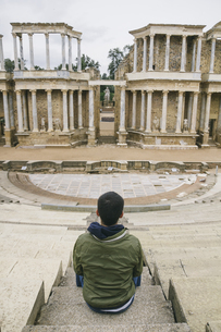 Spain, Merida, back view of man sitting in front of Roman thの写真素材 [FYI04333787]