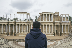 Spain, Merida, back view of man sitting in front of Roman thの写真素材 [FYI04333790]