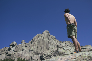 Spain, shirtless climber using his chalk bag in front of theの写真素材 [FYI04333794]