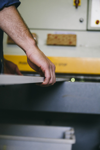 Worker putting a wooden board on sander machine in a carpentの写真素材 [FYI04333799]