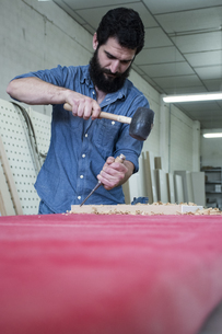Carpenter using a chisel and hammerの写真素材 [FYI04333802]