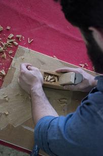 Hands of a carpenter using a hand planeの写真素材 [FYI04333804]