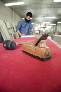 Carpenter tools with unfocused carpenter sanding a wood planの写真素材 [FYI04333806]