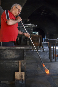 Man blowing with a tube molten glass in a glass factoryの写真素材 [FYI04333827]