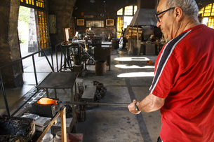 Man working with molten glass in a Factory in Mallorcaの写真素材 [FYI04333829]