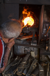 Man blowing glass with a tube using a furnace in a glass facの写真素材 [FYI04333830]