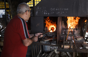 Man using a furnace in a glass factory in Mallorcaの写真素材 [FYI04333831]