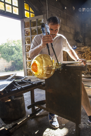 Man working with molten glass using a tweezers in a glass faの写真素材 [FYI04333836]