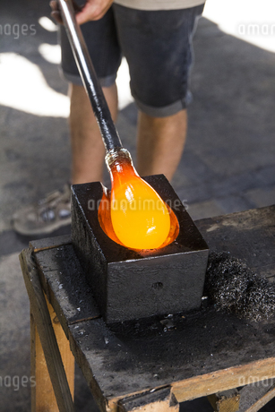Man putting molten glass in a mold in a glass factoryの写真素材 [FYI04333841]