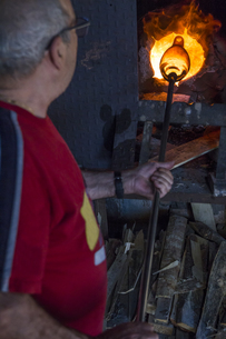 Man using a furnace in a glass factoryの写真素材 [FYI04333844]