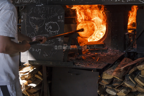 Man using a furnace in a glass factoryの写真素材 [FYI04333847]