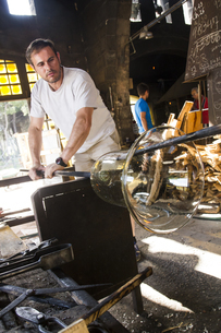 Man working with molten glass in a glass factoryの写真素材 [FYI04333848]