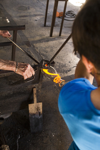 Men working with molten glass in a glass factoryの写真素材 [FYI04333850]
