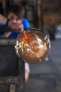 Man blowing molten glass with a tube in a factoryの写真素材 [FYI04333852]