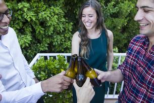 Friends toasting with bottles of beer in a gardenの写真素材 [FYI04333857]