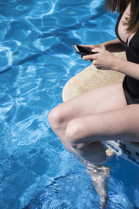 Woman sitting on the edge of a pool refreshing with her legsの写真素材 [FYI04333859]