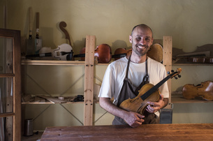 Smiling luthier holding a violin in his workshopの写真素材 [FYI04333861]