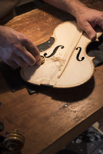 Luthier using a mini hand plane on the top plate of a violinの写真素材 [FYI04333863]