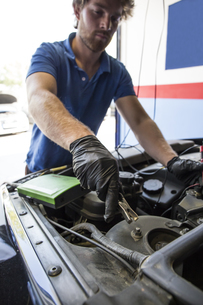 Mechanic placing a battery clip in a carの写真素材 [FYI04333878]