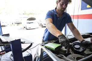 Mechanic placing a battery clip in a carの写真素材 [FYI04333880]