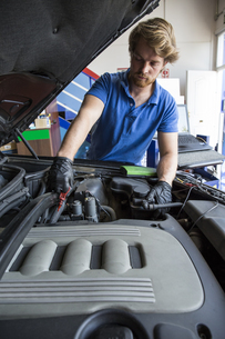 Mechanic checking the oil of a carの写真素材 [FYI04333881]