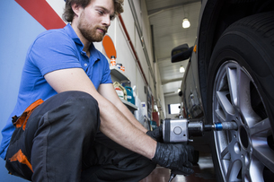 Mechanic fixing a car wheel in a workshopの写真素材 [FYI04333882]