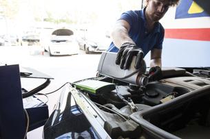 Mechanic refilling oil in a carの写真素材 [FYI04333883]