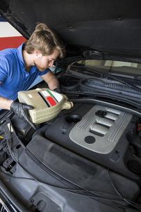 Mechanic refilling oil in a carの写真素材 [FYI04333884]