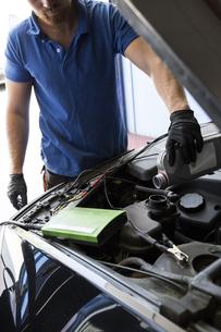Mechanic refilling oil in a carの写真素材 [FYI04333885]