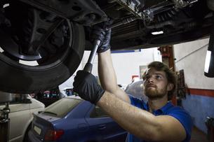 Mechanic fixing suspended car in his workshopの写真素材 [FYI04333887]