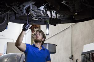 Mechanic fixing suspended car in his workshopの写真素材 [FYI04333888]