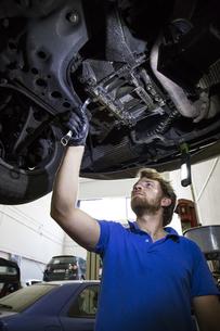 Mechanic fixing suspended car in his workshopの写真素材 [FYI04333889]