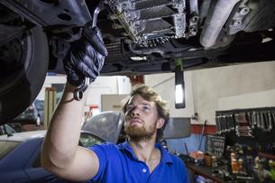 Mechanic fixing suspended car in his workshopの写真素材 [FYI04333890]