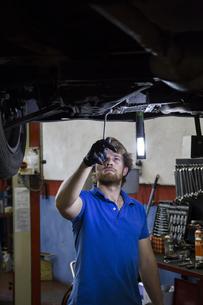 Mechanic fixing suspended car in his workshopの写真素材 [FYI04333891]