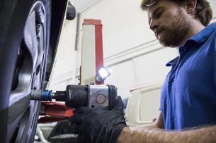 Mechanic fixing a car wheel in a workshopの写真素材 [FYI04333892]