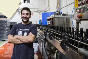 Man standing next to conveyor belt in bottling plantの写真素材 [FYI04333931]