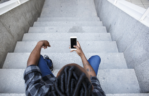 Young man sitting on stairs, using smart phoneの写真素材 [FYI04333934]