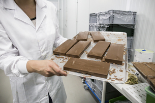 Woman holding a tray with chocolate nougat in a chocolate faの写真素材 [FYI04333959]