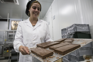 Woman holding a tray with chocolate nougat in a chocolate faの写真素材 [FYI04333961]