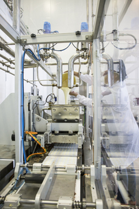 Woman pouring liquid white chocolate in a machine in a chocoの写真素材 [FYI04333962]