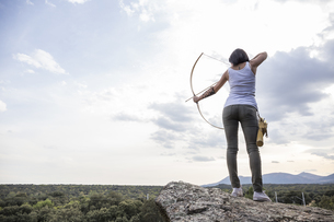 Archeress standing on a rock aiming with bowの写真素材 [FYI04333965]