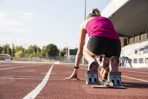 Female runner on tartan track in starting positionの写真素材 [FYI04333972]
